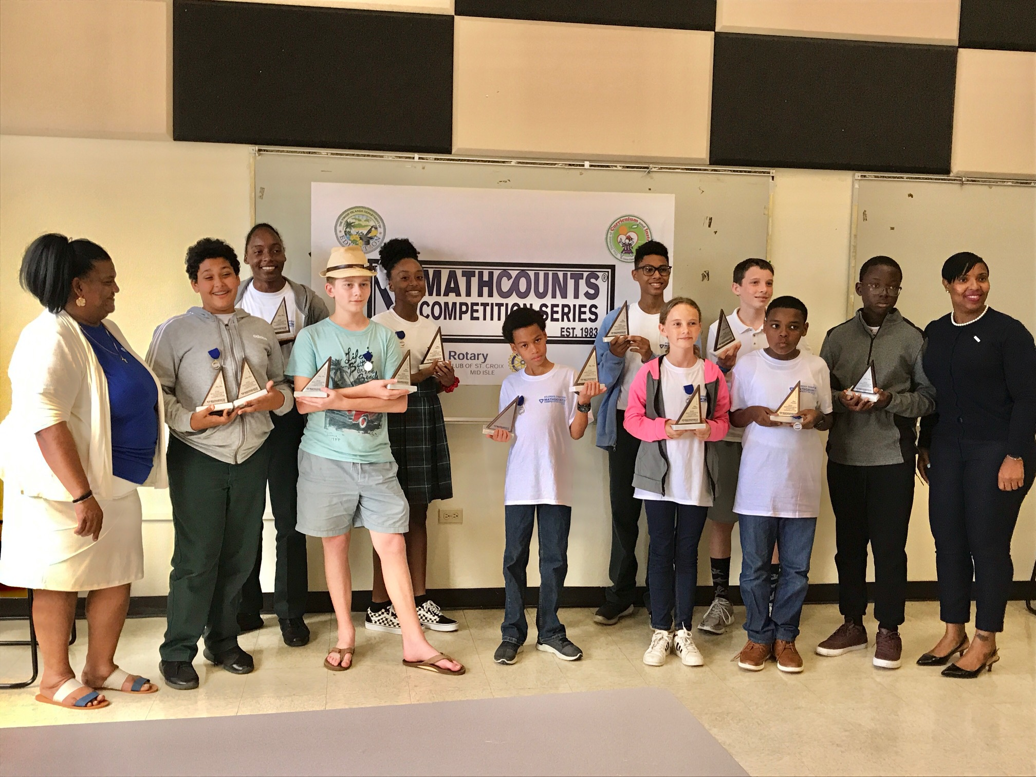 STX MathCounts Top 10 Students with Coordinator & Deputy Commissioner - From left: STX Math Coordinator Juanita Boneque, Samir Boucenna, Zanyja Rodriguez, Andrew Thompson, Kristina Horsford, Keemar Crosky, Jaden Gonzalez, Lauren Jones, Nick Turk, Aundre Dolcar, Michael Atwell, and Deputy Commissioner Carla Bastian. (Source Photo by Elisa McKay)